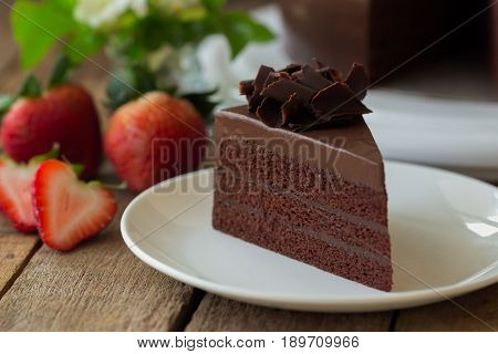 Homemade bakery cake : chocolate fudge cake decorated with chocolate curl. Triangle slice piece of chocolate cake on rustic wood table for cafe ,meeting coffee break or tea time. Chocolate cake is the most popular cake for birthday gift.