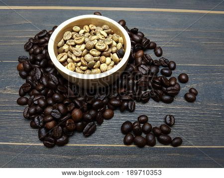 Raw coffee beans in a wooden cup with roasted coffee beans on dark wodden table