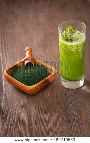 Green smoothie with spirulina on wood background