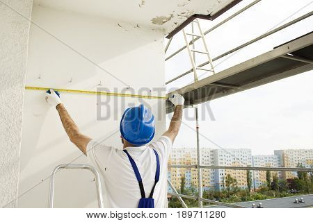 The construction worker's hands measure distance measure. Construction work.