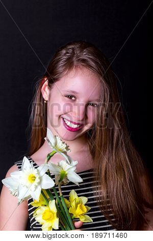 Teen girl holding a bouquet of daffodils and smiles . Portrait on a dark background. A vertical image. Girl in striped dress with her hair