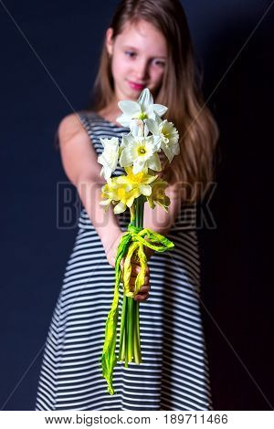 Bouquet of yellow and white daffodils in the hands of the girls. Portrait on a dark background. Vertical image. Focus on a bouquet of flowers. Girl in striped dress with her hair on a background