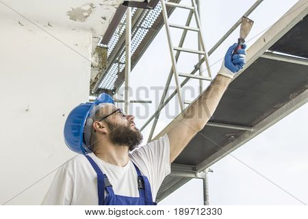 A construction worker in a work attire, protective gloves and a helmet on the head gives a spatula. Work at high altitude. Scaffolding in the background.