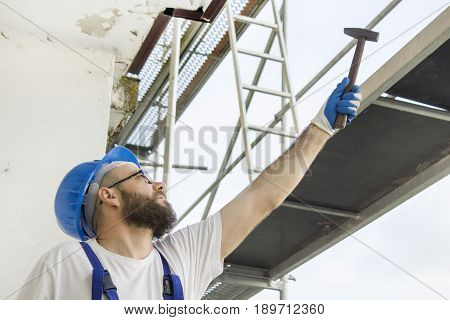 A construction worker in a work attire, protective gloves and a helmet on the head gives a hammer. Work at high altitude. Scaffolding in the background.
