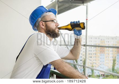 A construction worker in work wear, protective gloves and a helmet on the head drinks beer from the bottle. Work at high altitude. Scaffolding in the background.