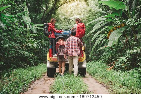 Happy asian young travellers with 4WD drive car off road in forest young couple walking with backpacks and another two are enjoying on 4WD drive car. Young mixed race Asian woman and man.