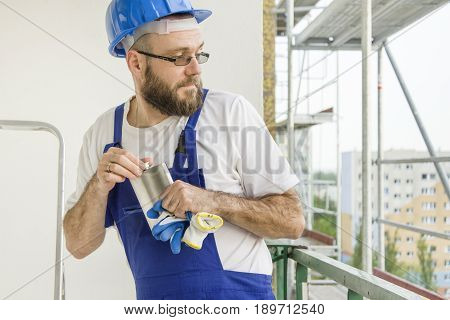 A construction worker in a work outfit and a helmet on the head carefully unscrews an alcohol bottle carefully looking behind him. Work at high altitude. Scaffolding in the background.