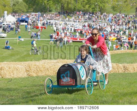STOCKHOLM SWEDEN - MAY 21 2017: Mother push her son up a hill in a home made soapbox car in the race Gardesloppet at Djurgarden Stockholm Sweden. May 21 2017