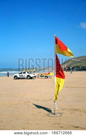 Newquay, Cornwall, Uk - April 7 2017: Red And Yellow Lifeguard Flags On The Beach For Swimmers And S