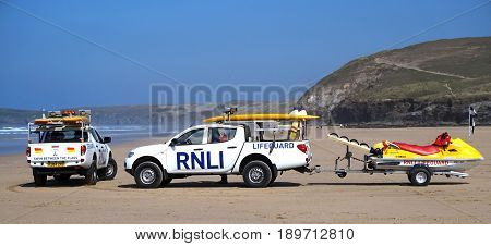 Newquay, Cornwall, Uk - April 7 2017: Rnli Lifeguard Trucks And Jetski On A Cornish Surfing Beach At
