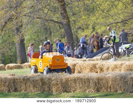 STOCKHOLM SWEDEN - MAY 21 2017: Boy driving a home made soapbox car downhill on a field people in the background in the race Gardesloppet at Djurgarden Stockholm Sweden. May 21 2017