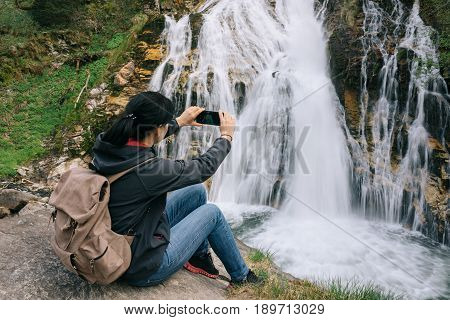 A Girl Is Taking Pictures Of A Waterfall On A Mobile Phone Camera In The Alpine Mountains