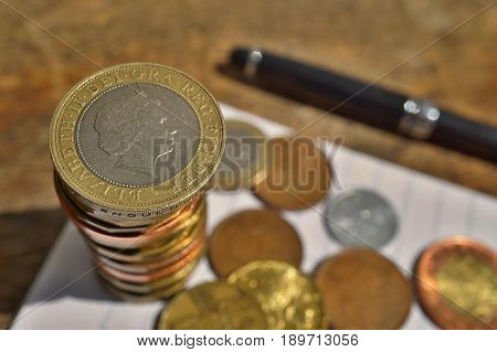 Macro detail of a silver and golden coin in a value of two British Pounds Sterling on the top of coins' pile in a business background white lined pad, black pen a randomly spread small change