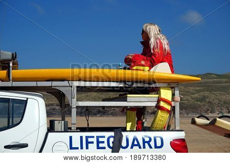 Newquay Cornwall UK - April 7 2017: Female RNLI lifeguard keeping watch on top of a truck on a surfing beach in Newquay