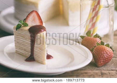 Homemade crepe cake and strawberry sauce decorate with strawberry. Triangle slice of crepe cake. French dessert: crepe cake for tea time,cafe or coffee break and birthday party. Delicious homemade crepe cake. Sweet cake for relaxing time.