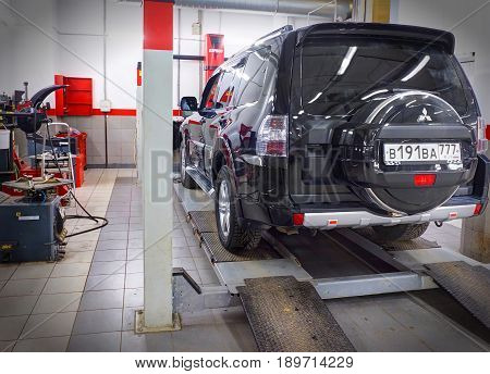MOSCOW, MAR,02, 2017: Car automobile at wheel alignment maintenance works repair at automotive service center workshop. Technical maintenance wheel alignment correction fixation MOT. Car maintenance