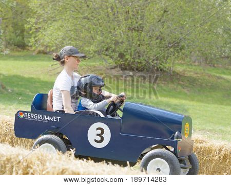 STOCKHOLM SWEDEN - MAY 21 2017: Smiling boy and mother driving a green soapbox car downhill on a field in the race Gardesloppet at Djurgarden Stockholm Sweden. May 21 2017