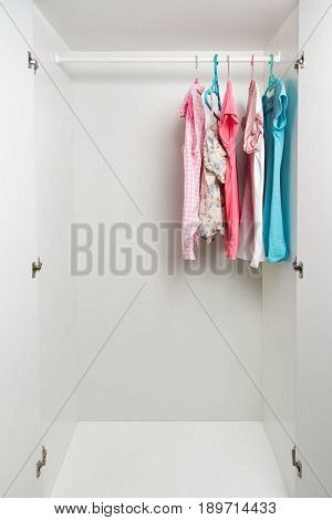 Clothes Hanging On Rail In White Wardrobe.