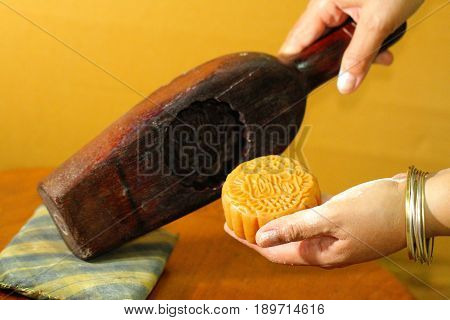 closed up hand of Chef who is removing moon cake from wooden mould, preparing moon cake, food stylish, menu, backgrounds