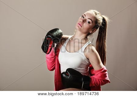 Feminist and emancipation idea. Woman in male occupation training boxing. Fit female fitness girl doing exercise on grey background.