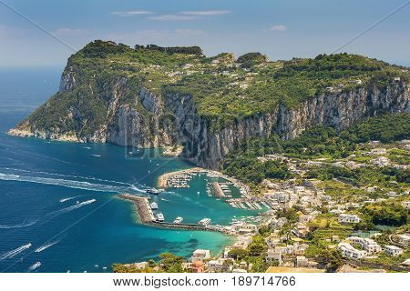 aerial view of italian holiday island Capri with picturesque marina and Tyrrhenian sea in background, Capri island, Campania region, Italy