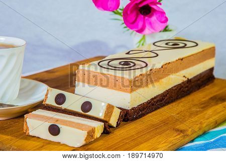 Holiday cake Three-colate. Three-layer chocolate cake, decorated with chocolate patterns. Background - white vase with flowers. Professional bakery