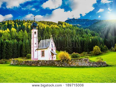 The summer sunset, Dolomites, Tirol. The famous church of St. Mary Magdalene and bell tower in a mountain valley. The concept of eco-tourism