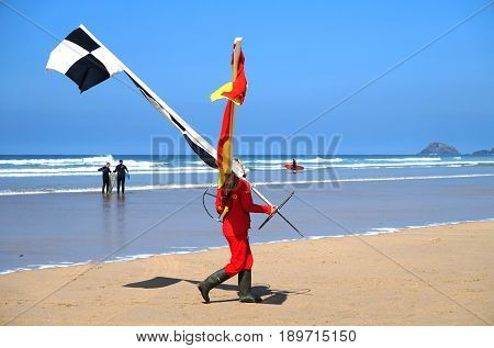Newquay, Cornwall, Uk - April 7 2017: Female Rnli Lifeguard Moving The Swimming And Surfing Zone Fla