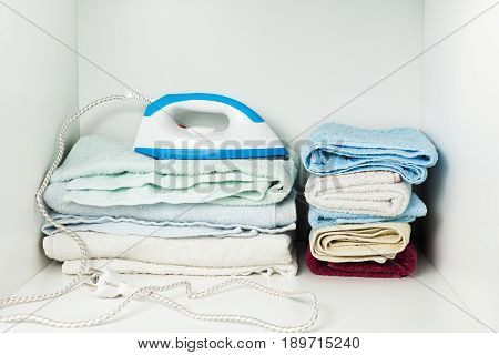 Iron And Towels In White Wardrobe.
