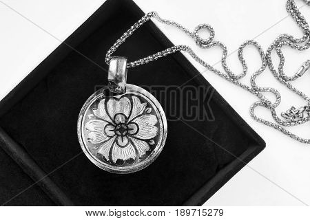 Vintage silver medallion on a chain in jewel box closeup
