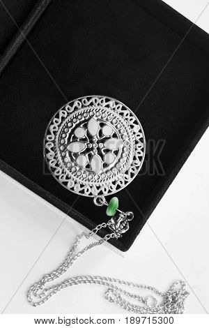 Ethnic silver carved medallion in black jewel box closeup
