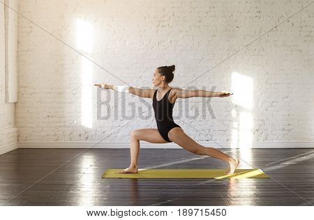 Attractive asian young woman practicing yoga asana Warrior II Pose in a training hall background. Sports shapely female in Virabhadrasana II pose during yoga class in a gym. Yoga and health concept.