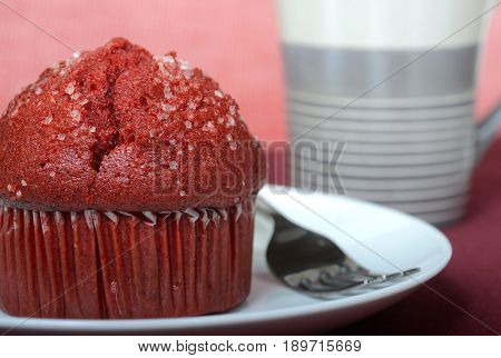 Warm delicious red velvet muffin served on a plate with a cup of coffee