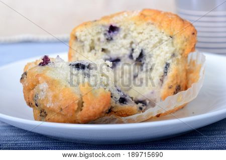 Delicious fresh blueberry muffin pulled open showing the ripe blueberries inside