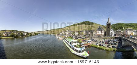 People Enjoy The River Cruise On River Moselle With View To Old Historic Town Of Bernkastel-kues