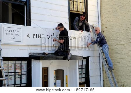 Padstow, Cornwall, Uk - April 6Th 2017: Workmen Fitting A New Sign To The