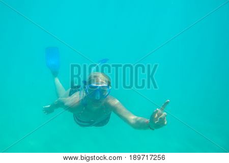 Female apnea swims in tropical sea with american flag bikini. Underwater background of a woman snorkeling and doing skin diving. Watersport activity in Hawaii. Tropical destination holiday travel.