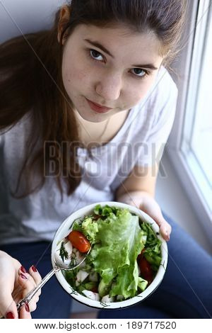 teenager girl vegan with green salad bowl close up photo