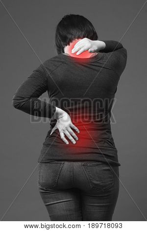 Back pain woman with backache on gray background with red dots