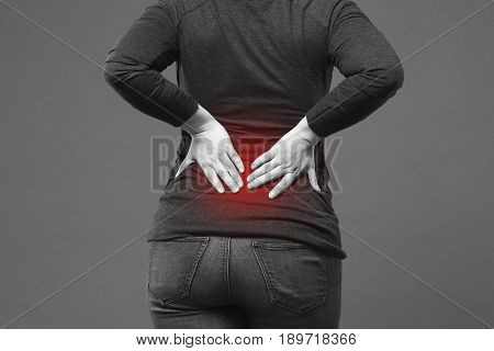 Back pain kidney inflammation ache in woman's body close-up on gray background with red dot