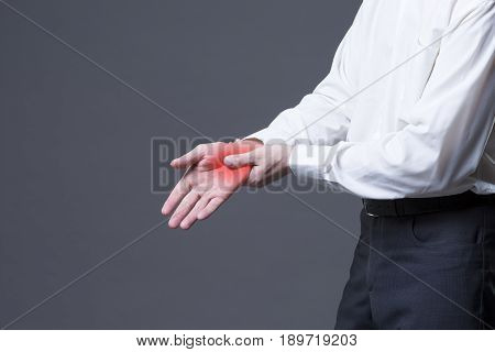 Pain in hand joint inflammation carpal tunnel syndrome studio shot with red dot on gray background