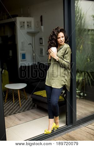 Modern Woman Standing Next To A Glass Door And Drinking Coffee