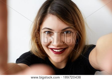 Charming european girl with pretty smile taking selfie on her mobile phone. Young joyful girl holding a smartphone digital camera with her hands and taking a selfie portrait. Casual lifestyle photo.
