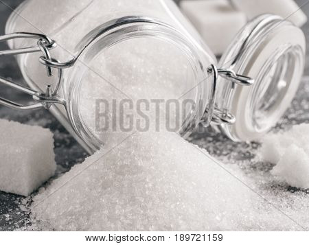 Close up view of white sugar on gray galvanized iron background. Granulated sugar in glass jar and sugar cubes. Sugar background. Copy space. poster