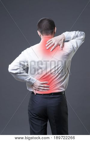 Back pain man with backache on gray background with red dots