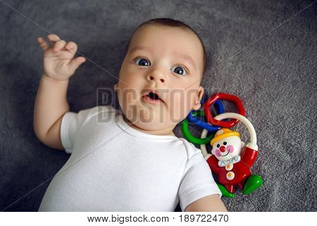 newborn to three months lying in bed and lying next to a colorful rattle