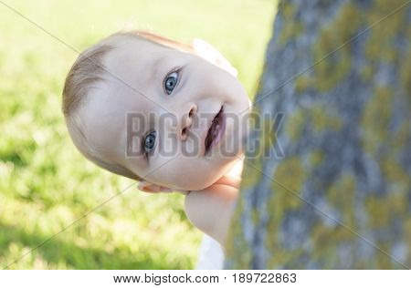 1 year baby boy playing hide-and-seek on swimming pool grass. Baby development concept