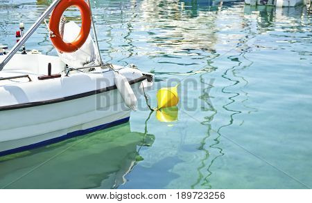 fishing boat with yellow buoy reflected on sea Aegina island Greece