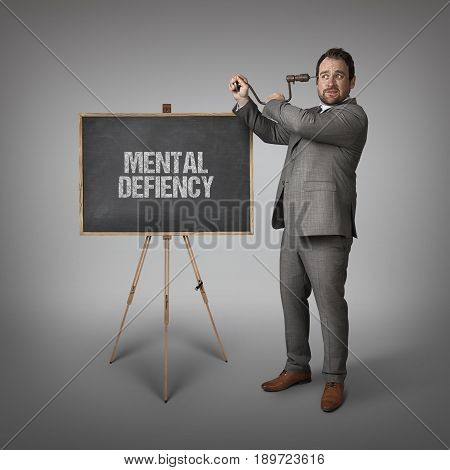 Mental defiency text on blackboard with businessman drilling his head