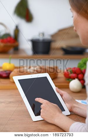 Haman hands  using touch pad in the kitchen. Closeup of woman making online shopping by tablet computer and credit card.  Cooking and shopping concept